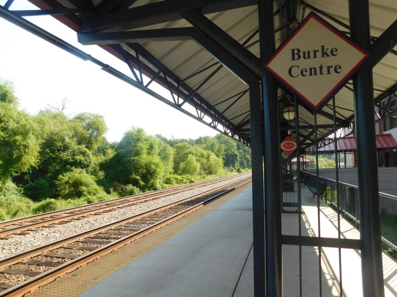 Image of Burke Center Train Station, with tracks and greenery to the left of the platform