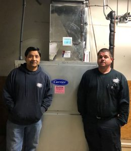 Two Burke technicians standing in front of a newly installed unit.