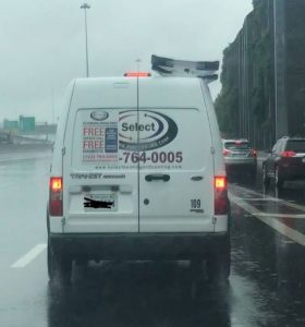 DM Select Services service truck on the road in the pouring rain.