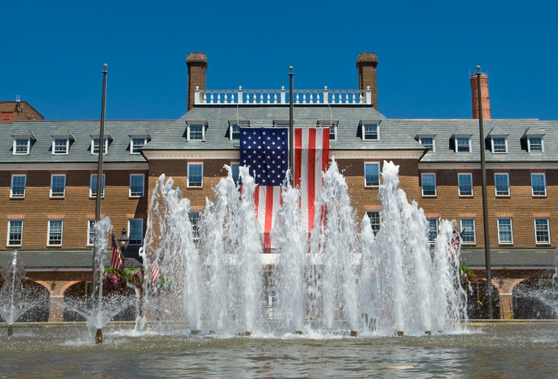 Photo of colonial city hall in Alexandria, VA, displaying a huge American flag with fountains in the foreground.