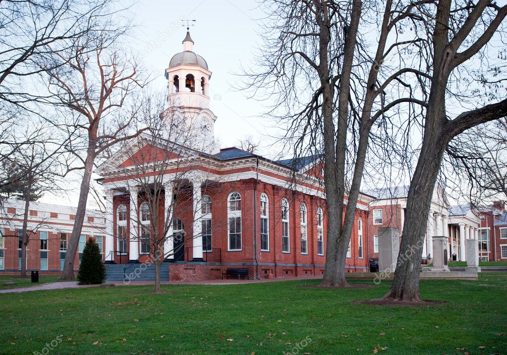 Photo of the old courthouse in Leesburg during autumn, with its red brick walls, white columns in front, and picturesque white bell tower.