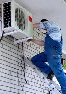Image shows a technician up on a ladder repairing an air con unit outside of the house.