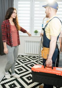 Young woman in winter attire pointing technician to a radiator on the wall.