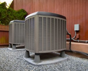 Compressors for air conditioning unit sitting on a concrete base and gravel-covered enclosed area.