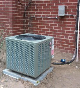 Image of an AC unit outside a brick home.