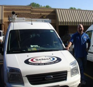 HVAC technician smiling and ready to go, next to DM Select Services vehicle.