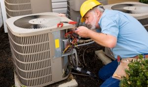 Image shows an air con technician checking the wiring of the air conditioning unit.