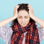 A young Asian woman with a red and black plaid neck scarf has her hands on her head and is grimacing. It looks like either she has a headache, or she is frustrated by something and doesn't know what to do.
