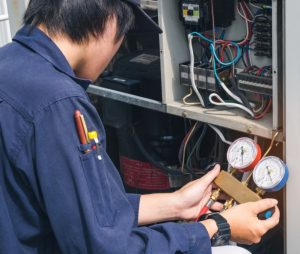 The image shows a furnace repairman checking electrical gauges.