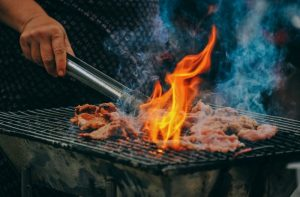 Picture shows a barbeque grill with meat and flames, and a man's hand using tongs to move the meat.