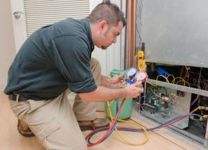 HVAC technician is working on repairing a unit.